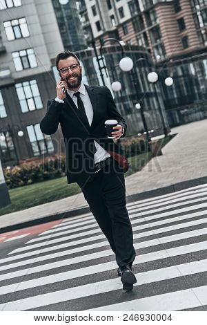 Confident Businessman. Full Length Of Young Man In Full Suit Talking On The Phone And Smiling While
