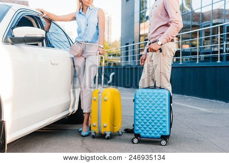 Partial View Of Husband And Wife With Baggage Standing At Car On Parking