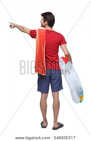 Rear view of a man in shorts with an inflatable circle points his hand upwards. Rear view people collection.  backside view of person.  Isolated over white. Young guy showing something on the beach