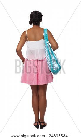 Back view of a young African-American with a beach bag girl  watching. Rear view people collection.  backside view of person. Isolated over white background.