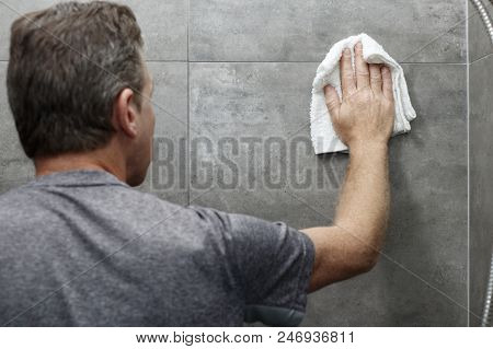 Male Scrubbing A Home Bathroom Gray Tile Shower Wall With His Hand Holding A Wet White Cotton Rag. W