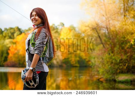 Photo Of Smiling Woman With Backpack And Bicycle Helmet Standing Sideways Against Background Of Lake