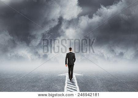 Back View Of Younf Businessman Following Arrow Direction On Dull Cloudy Sky Background. Choice And C