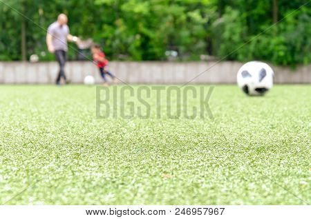 Football Lawn, Father And Kid Playing In Back. Soccer Closeup Detail Wallpaper Texture.
