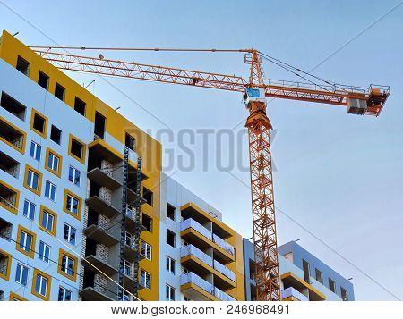 Construction Site. Construction Crane Near Building Under Construction Against Blue Sky.