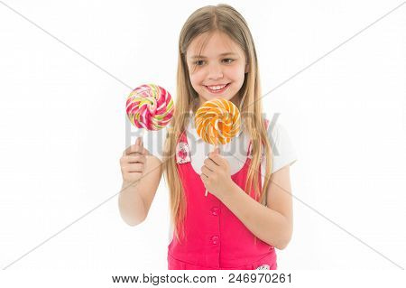 Hard Choice. Cheerful Little Girl Holding Lollipops In Her Hands And Smiling While Standing Isolated