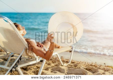 Beautiful Young Woman Enjoying On The Beach. She Is Lying On Sunbed, Holding Summer Hat And Sunbathi