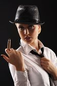 Young attractive female gangster smoking cigar over dark background poster