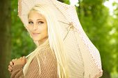 Enigmatic Beauty With Umbrella beautiful blonde female model posing in park under polka dot umbrella. poster
