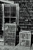 Lobster traps sitting outside a fish house in new england. poster