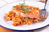 Salmon steak with thyme and noodle salad on a plate poster