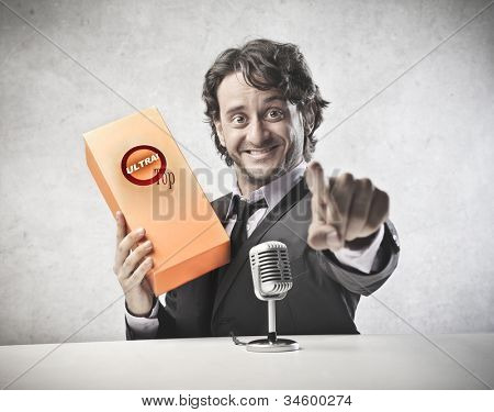 Smiling announcer advertising a product in front of a microphone