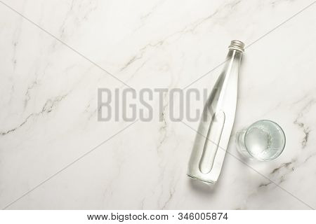 Glass Bottle Of Water And A Glass Of Water On A Marble Table. The Concept Of Heat, Water Balance, Di