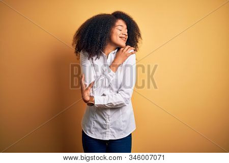 Young beautiful african american elegant woman with afro hair standing over yellow background Hugging oneself happy and positive, smiling confident. Self love and self care