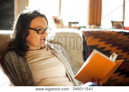 An everyday woman reading a book at home.