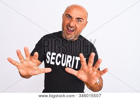 Middle age safeguard man wearing security uniform standing over isolated white background afraid and terrified with fear expression stop gesture with hands, shouting in shock. Panic concept.