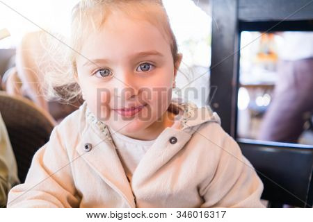 Beautiful toddler child girl sitting on baby highchair laughing