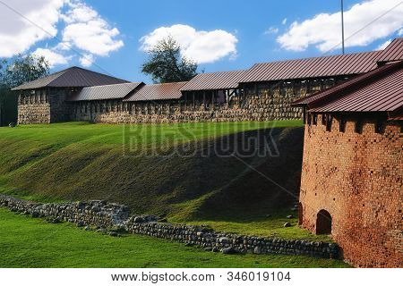 Fragment Of An Old Fortress Wall Made Of Stone On An Earthen Rampart Covered With Green Grass In The