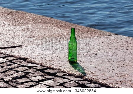St.petersburg, Russia - June 30, 2019: Empty Green Glass Beer Bottle On A Granite Promenade Without