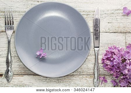 Spring Table Setting With Plate Fork And Knife Decorated With Lilac Flowers On White Wooden Backgrou