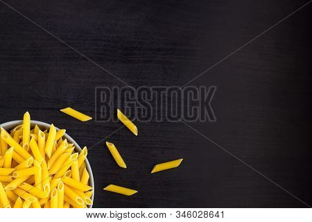 Top View Of Black Background With Italian Raw Penne Or Pasta In Bowl With Copy Space