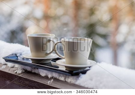 Steaming Hot Coffee In Two Mugs, Buried In Snow, On A Balcony, On A Bright Winter Morning. Breakfast