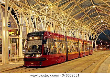 Lodz / Poland. 18 July 2019:  Modern Tram Riding Around Evening City. Red Tram Going On City Street