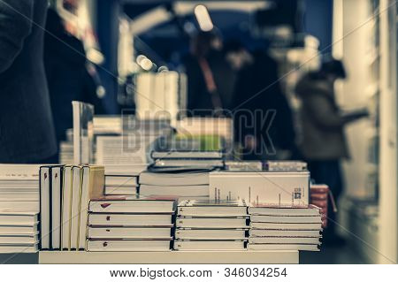 Pile Of Books, Abstract Blurred Background In Book Store Or In Library. Unrecognizable People, Books