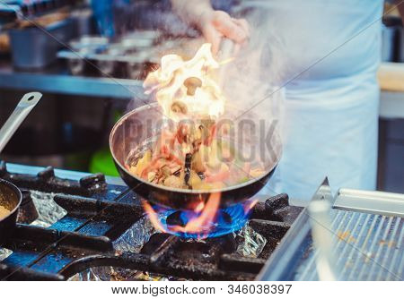 Chef cooking in a restaurant kitchen with flames of fire on his pan