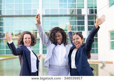 Team Of Cheerful Businesswomen Raising Hands. Group Of Happy Multiethnic Female Colleagues Triumphin