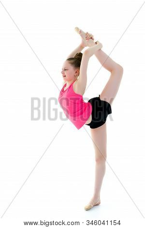 A Girl Gymnast Balances On One Leg.the Concept Of Childhood, Sport, A Healthy Lifestyle. Isolated On