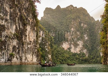 Surat Thani, Thailand - February 13, 2019: Riding traditional thai longtail boat on Cheow Lan lake in Khao Sok National Park, Thailand