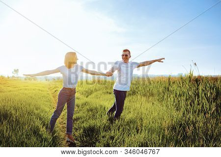 Holidays, Vacation, Love And Friendship. Smiling Couple In White T-shirts, Sunglasses And Jeans Spre