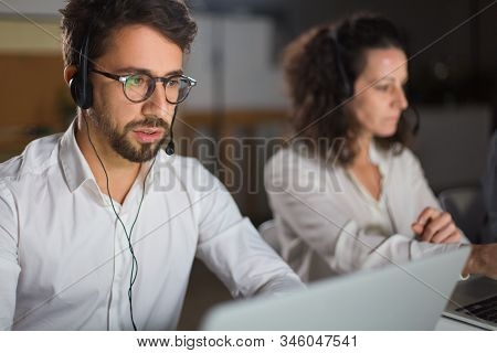 Front View Of Call Center Operator Communicating With Client. Confident Young Man In Eyeglasses Look