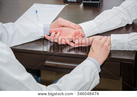 Young Doctor Checking Pulse Of Elderly Woman In Clinic.