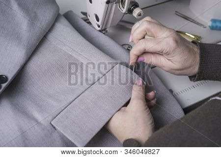 Master Couturier, Against The Background Of A Sewing Machine, Sews Clothes From High Quality Fabric,