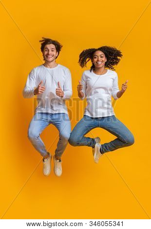 Everything Cool. Joyful Interracial Couple Jumping In The Air And Gesturing Thumbs Up, Expressing Po