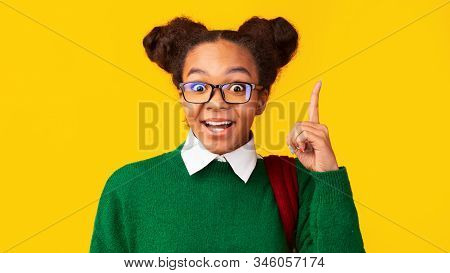 Aha Moment. Headshot Of Excited Black Girl With Opened Mouth Pointing Finger Up At Studio, Copyspace