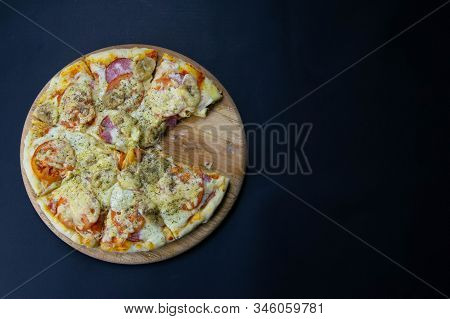 Pizza With Salami, Mozzarella, Tomatoes, Bananas Stands On A Wooden Board, On The Black Background.