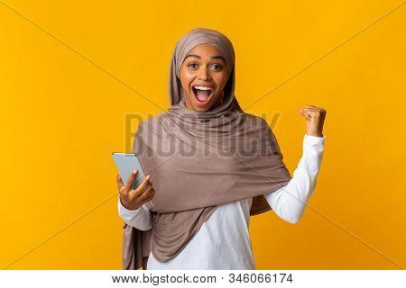 Online Win. Overjoyed Black Muslim Girl In Headscarf Celebrating Success With Smartphone, Raising Fi