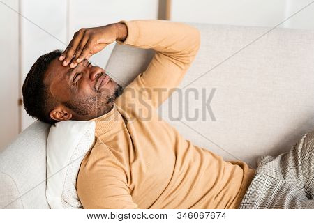Headache. African American Man Having Migraine Touching Forehead Suffering From Pain Lying On Couch