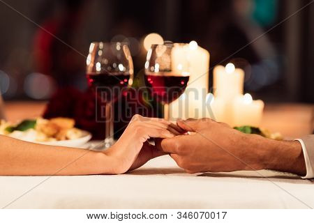 Romance And Love. Closeup Of Couple Holding Hands On Served Restaurant Table With Wine, Candles And