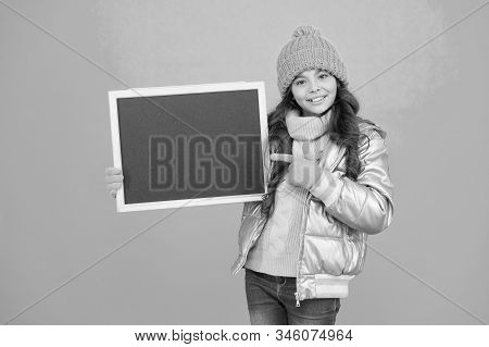 Promotion Concept. Kid Cheerful Promoting. Smiling Girl Wear Winter Outfit Show Blank Chalkboard Cop