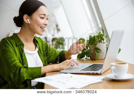 Smiling beautiful young asian woman working on laptop computer while sitting at the cafe indoors, looking through documents