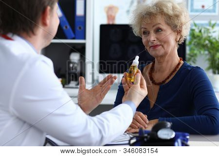 Portrait Of Aged Senior Female Consulting With Doctor. Therapeutic In Medical Gown Advising Cannabin