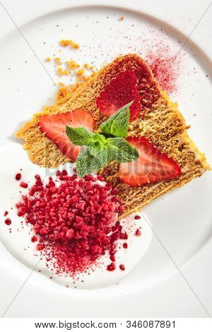 Traditional russian honey cake medovik on white restaurant plate isolated. A triangular slice of layered sponge caramel tart with fresh strawberries and mint topview