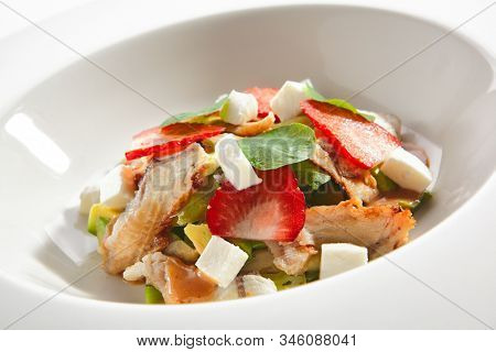 Salad with smoked eel fish, avocado, feta cheese and strawberries on restaurant plate isolated. Macro photo of delicious luxury seafood salat with unagi, broccoli and nasturtium leaves closeup