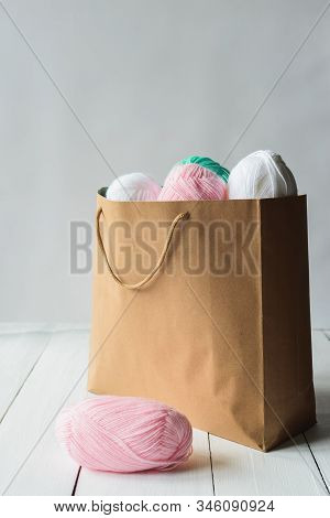 Oval Acrylic Colorful Wool Yarn Thread Skeins Lying Near And Into Kraft Paper Brown Package On White