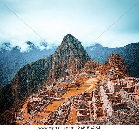 Breathtaking sunshine landscape of ancient majestic Machu Picchu city among high rocky mountains under the clouds
