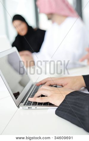 Arabic buisnessman is typing and writing on the laptop